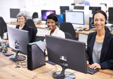 Cropped shot of three female call center representatives wearing headsets